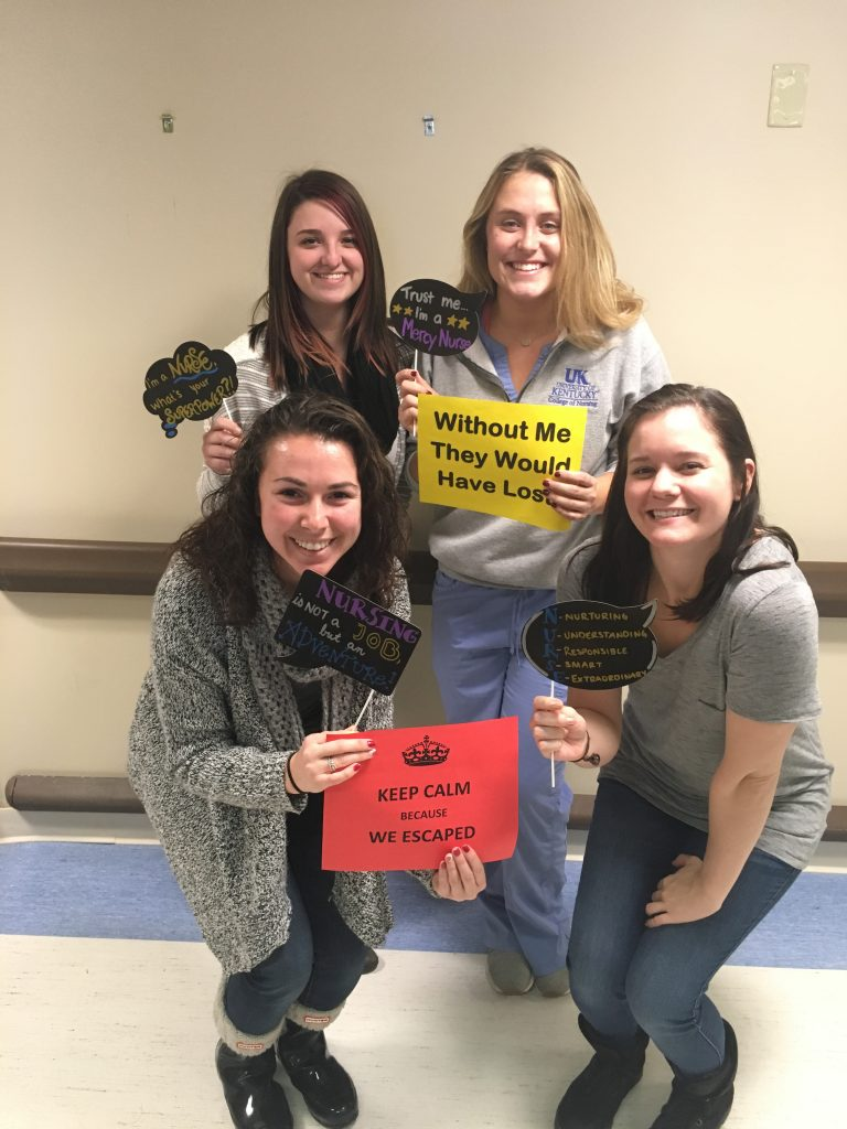 four Escape Room participants holding signs indicating they escaped and won the game