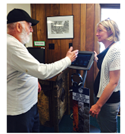 Anja Bouchard providing a demonstration of the emergency preparedness kiosk to a patron at Au Sable Free Library, photo