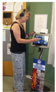 Jane Bouchard, Director at Schroon Lake Public Library, exploring the information on the kiosk, photo