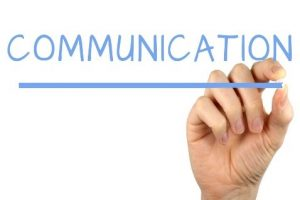 the word communication being underlined by a hand with a pen