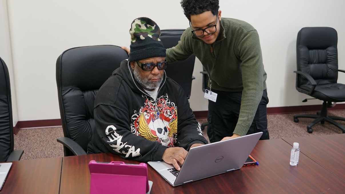 Jordan Owens, Computer Program Assistant, stands with an HACP resident who is typing on an open laptop.