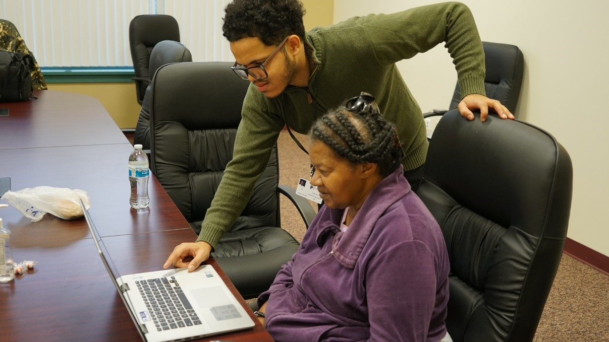 Jordan Owens, Computer Program Assistant, stands with an HACP resident who is sitting in front of an open laptop.