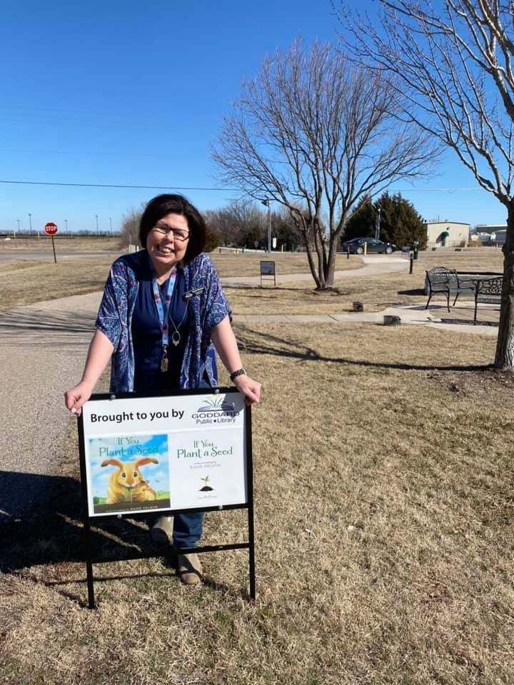 Photo of librarian in a field in front of a sign for the Fitness Friday program.