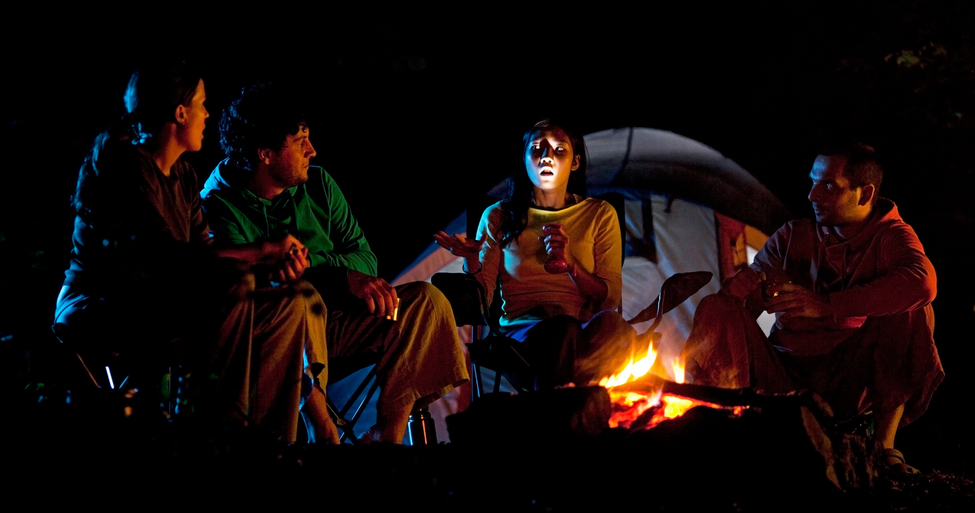 Friends at campfire telling stories