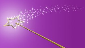 Gold magic wand with sparkles on purple background