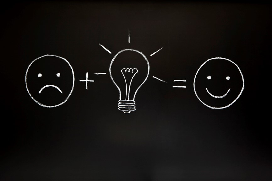 Diagram: sad face plus lightbulb equals happy face