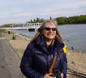 Susan Wolfe standing beside a river in Europe