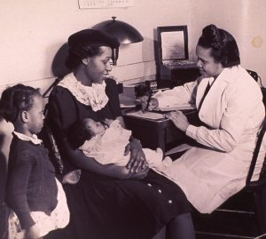 An African American nurse is recording a medical history as it is reported by a woman holding an infant.