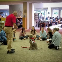 Student gather around therapy dog