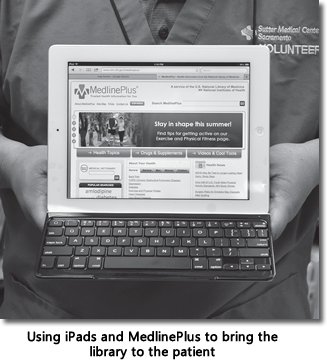 Person holding an iPad with a display of the MedlinePlus home page
