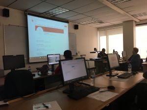 dimmed classroom with attendees sitting next to computers with a screen displaying a web page in front of the room