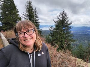 white woman with shoulder length blonde hair and glasses, wearing a black hoodie with pins. She is looking to the left on a vista with pine trees, water, and clouds in the background.