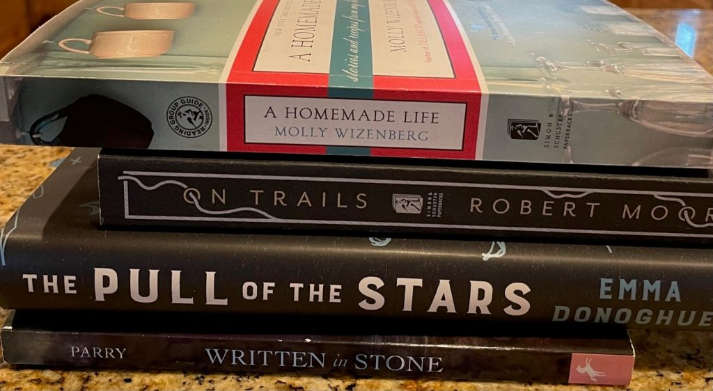 """This book spine poem reads, """"A Homemade Life, On Trails, The Pull of the Stars, Written in Stone."""""""