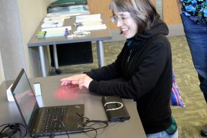Maddie (author of this post) kneeling at a table, attempting to use a projected keyboard, and Smyle Mouse software on a laptop